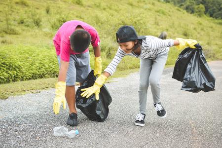 Niños mano en guantes amarillos recogiendo vacío de botella de plástico en la bolsa de bin, voluntario concepto Foto de archivo - 84183743