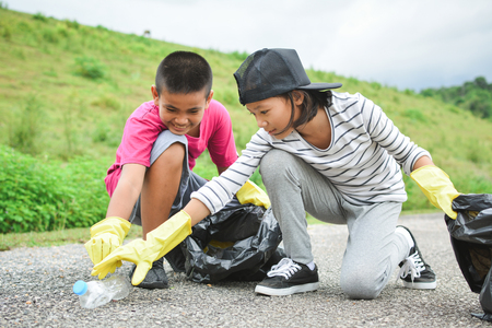 Children hands in yellow gloves picking up empty of bottle plastic into bin bag ,volunteer concept selective and soft focus
