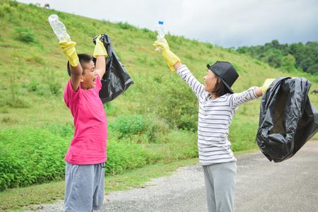 niños reciclando: Las manos de los niños en guantes amarillos recogiendo vacío de botella de plástico en la bolsa de bin, el concepto de voluntariado enfoque selectivo y suave Foto de archivo
