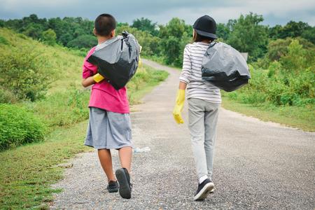 niños reciclando: Manos de niños en guantes amarillos recogiendo vacío de plástico de botella, concepto voluntario selectivo y enfoque suave Foto de archivo