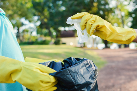 Hands in yellow gloves picking up empty of bottle plastic into bin bag ,volunteer concept Reklamní fotografie