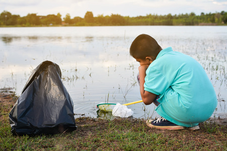 Boy hand in yellow gloves picking up empty of bottle plastic ,volunteer concept Stock Photo