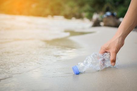 Übergeben Sie die Frau, die Plastikflaschenreinigung auf dem Strand, freiwilliges Konzept aufhebt