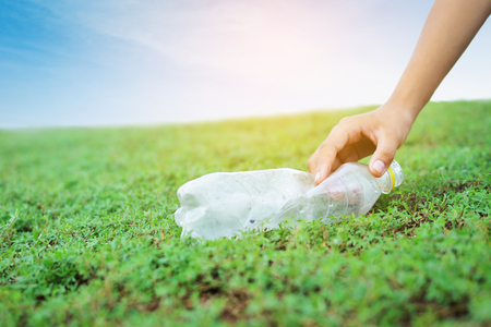 Hand picking plastic garbage on green grass