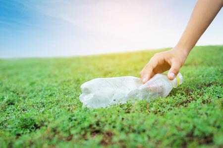 main ramasser des déchets en plastique sur l & # 39 ; herbe verte