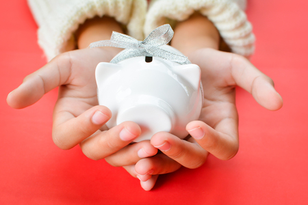 Hand of girl holding white piggy bank and ribbon type on red background with copy space ,concept save money