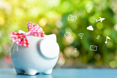 White piggy bank with icon on blue table and tree bokeh background concept save money