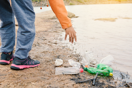 Boy picking up empty of bottle plastic ,volunteer concept
