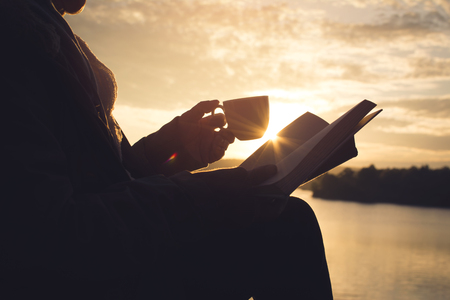 Silhouette of happy old women reading a book sitting on the rock near lake waiting for sunset relax time and holiday, color vintage style selective and soft focus Archivio Fotografico
