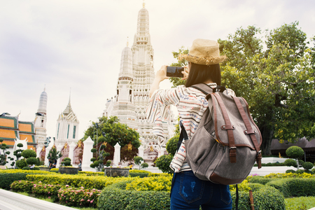 Asian woman tourist using smartphone shooting Wat Arun temple, Relax time on vacation hipster lifestyle
