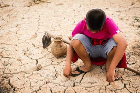 Menino sentado em chão seco quebrado, conceito de seca