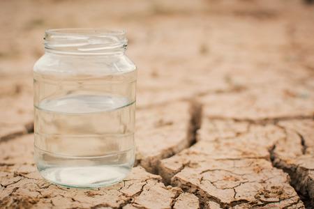 Frasco de vidro em terra seca rajada, conceito de seca e crise da água