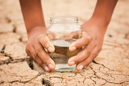 Mani del ragazzo che tiene il barattolo di vetro su terra asciutta incrinata, sulla siccità di concetto e sulla crisi dell'acqua