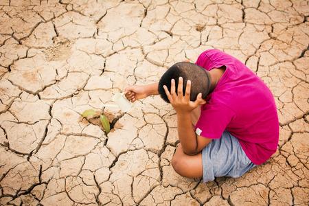 Menino regando pequena planta verde em terreno seco e seco, seca conceito e salve o mundo