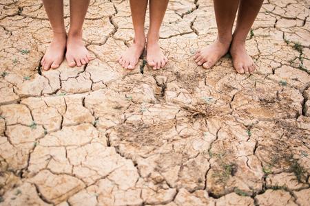 Pés às pessoas em terra seca quebrada. Confirme a esperança e a seca