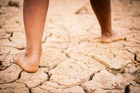 男孩的腳在破裂的干燥的地面。概念希望和乾旱
