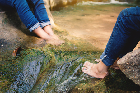 Feet of children in water on the forest, Relax time and vacation concept