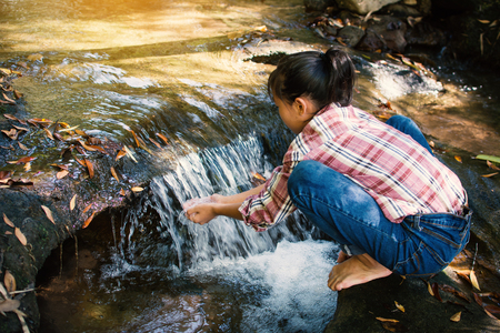 Cute girl drinking water from waterfall stream on forest