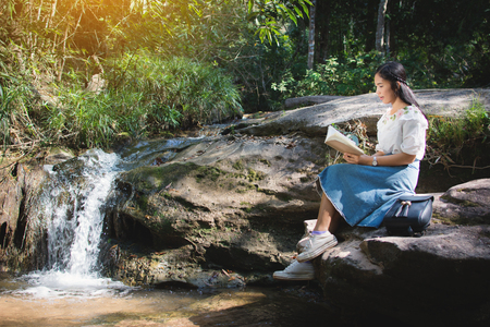Asian women reading a book sitting on the rock near waterfall in forest background  , Relax time and hobby on holiday , soft focus,tone of hipster style