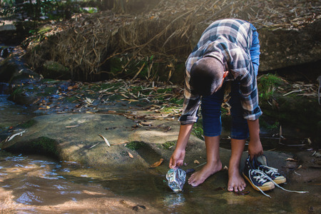 Boy picking up plastic garbage in forest ,volunteer concept Reklamní fotografie