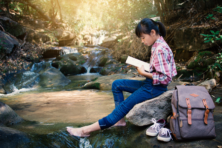 Asian girl reading a book sitting on the rock near waterfall in forest background  , Relax time and hobby on holiday concept backpacker, soft focus,tone of hipster style