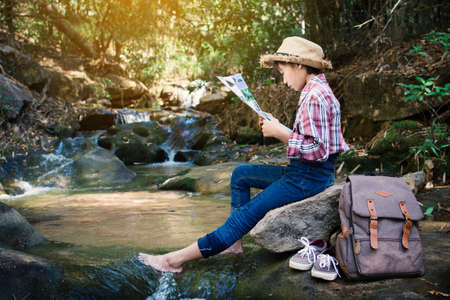 Asian girl looking a map sitting on the rock near waterfall in forest background  , Relax time on holiday concept backpacker,selective and soft focus,tone of hipster style