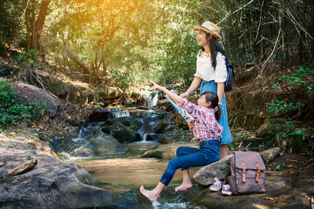 Asian woman and girl looking a map sitting on the rock near waterfall in forest background  , Relax time on holiday concept backpacker,selective and soft focus,tone of hipster style