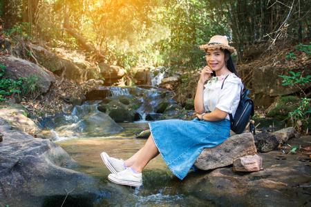 Mochileiro asiático de mulher sentada na rocha perto da cachoeira no fundo da floresta, Relaxe o tempo no feriado, foco seletivo e suave, tom do estilo hipster