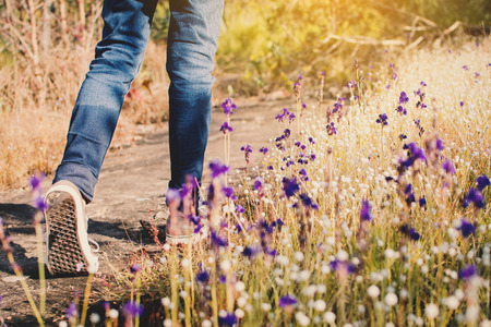 Feet of girl walking in beautiful flower filed background, Relax time on holiday