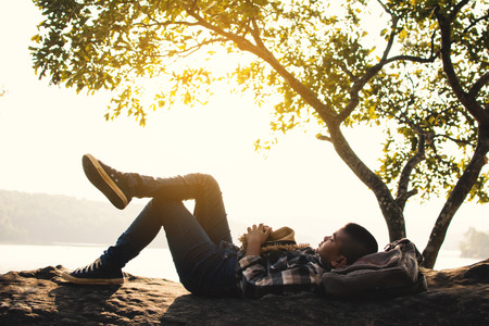 Boy backpacker sleeping on the rock in nature , Relax time on holiday concept travel,selective and soft focus,tone of hipster style Reklamní fotografie