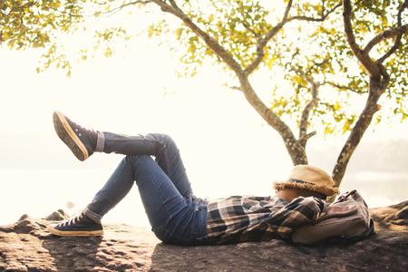 Boy mochileiro dormindo na rocha na natureza, relaxe o tempo no feriado conceito de viagem, foco seletivo e suave, tom de estilo hipster
