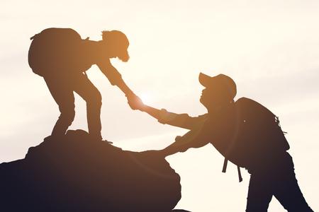 Silhueta de menina ajudando um menino na montanha superior no c
