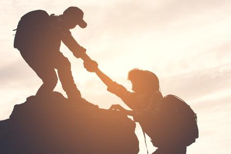 Silhueta de menino ajudando uma garota na montanha superior no c