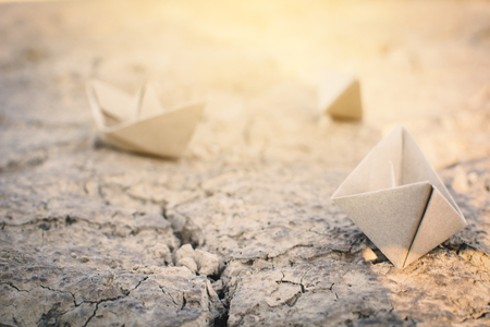 Paper boat on cracked ground, concept drought Stock Photo