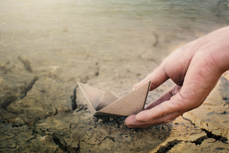 Hand holding paper boat on cracked ground, concept drought