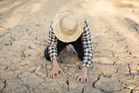Asian man sitting on cracked dry ground, concept drought and crisis environment