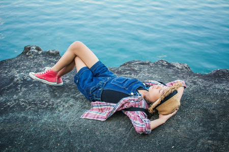 Cute girl sleeping on the rock in nature , Relax time on holiday concept travel,selective and soft focus,tone of hipster style Stock Photo