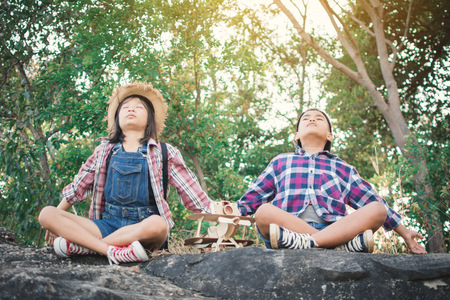 Asian girl and boy playing in nature , Relax time on holiday concept travel,selective and soft focus,tone of hipster style