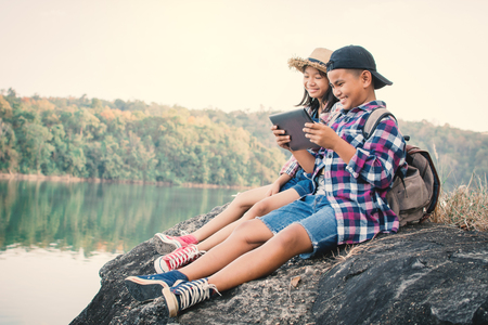 Asian children playing tablet in nature , Relax time on holiday concept travel,selective and soft focus,tone of hipster style