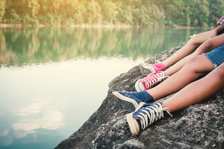 Feet of children sitting on the rock in nature , Relax time on holiday concept travel,selective and soft focus,tone of hipster style Stock Photo