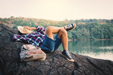 Boy backpacker sleeping on the rock in nature , Relax time on holiday concept travel,selective and soft focus,tone of hipster style Stock Photo