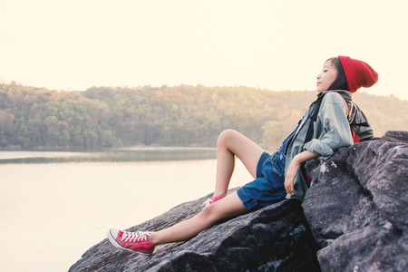 Asian girl backpack in nature , Relax time on holiday concept travel,selective and soft focus,tone of hipster style Stock Photo