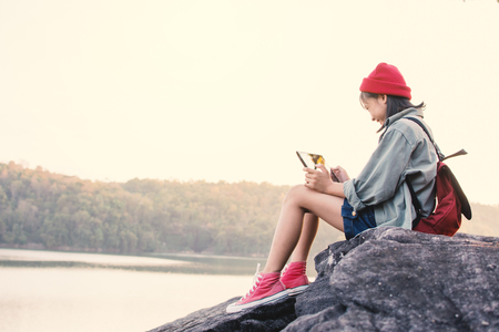 Asian girl playing tablet in nature , Relax time on holiday concept travel,selective and soft focus,tone of hipster style