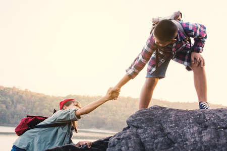 Boy helping a girl on the top mountain in nature Stock Photo
