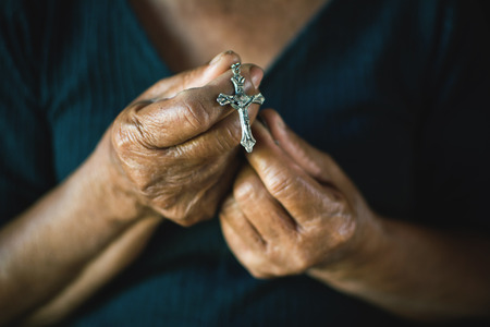 Close up of old hands praying on black background, Concept hope and worship Stock Photo