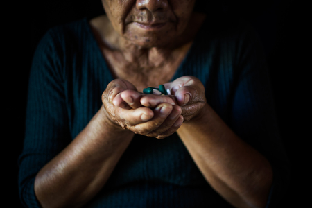 Old woman take a pill on black background, concept illness and healthcare