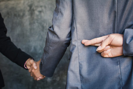 Businessman shake hand and betray , selective of focus and blue background