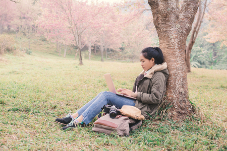 Enjoying moment woman backpacker using laptop in beautiful forest background, Relax time and work anywhere concept  ,color of vintage tone and soft focus Stock Photo