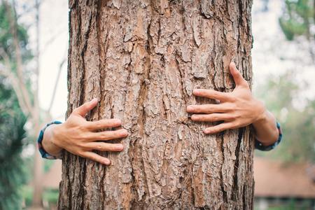 Homme câlin grand arbre couleur de hipster ton flou sélectif, concept nature et les gens protègent l'environnement