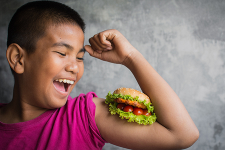 Portrait Asian fat boy enjoy eating with hamburger, concept healthy and lose weight ,selective and soft focus Foto de archivo